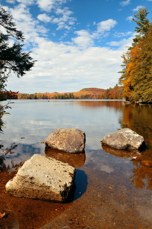 autumn colour: Lake with Autumn foliage, rock and mountains in New England Stowe