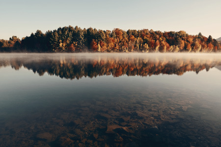 fog: Lake fog with Autumn foliage and mountains with reflection in New England Stowe