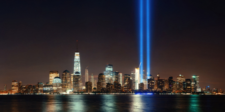 New York City downtown skyline at night panorama over Hudson River and September 11 tribute light 免版税图像