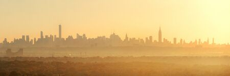city of sunrise: New York City sunrise silhouette viewed from park with fog panorama