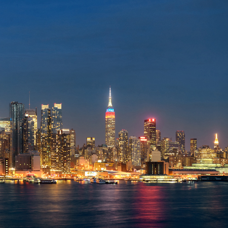 hudson river: Midtown skyline over Hudson River in New York City with skyscrapers at night Stock Photo