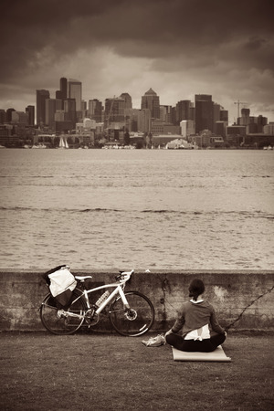 city buildings: Girl doing yoga at waterfront in Seattle in an overcast day. Stock Photo