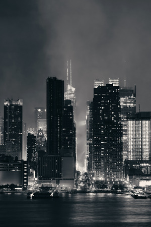 new york at night: Manhattan midtown skyscrapers and New York City skyline at night with fog Stock Photo