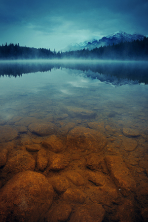 banff national park: Lake Herbert in a foggy morning with glaciers mountain and reflection in Banff National Park, Canada