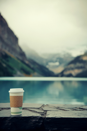 louise: Lake Louise with coffee cup in Banff national park with mountains and forest in Canada.