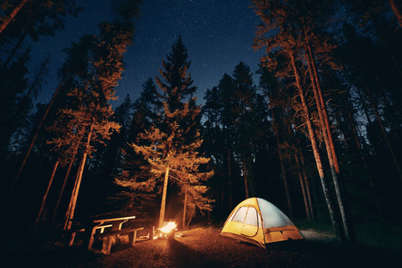 Camping under stars with bonfire and tent in Banff National Park Stockfoto