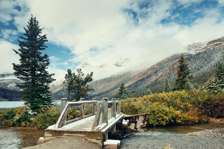 snow capped mountain: Wood bridge with snow capped mountain and forest in Banff National Park