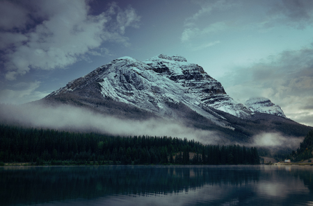 cloud capped: Snow capped mountain with lake reflection in a foggy dusk in Banff National Park, Canada.