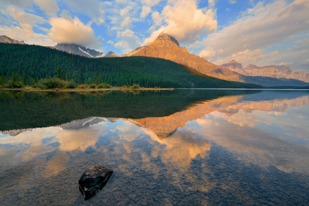 waterfowl: Waterfowl Lake sunrise with water reflection of mountains and cloud in Banff National Park