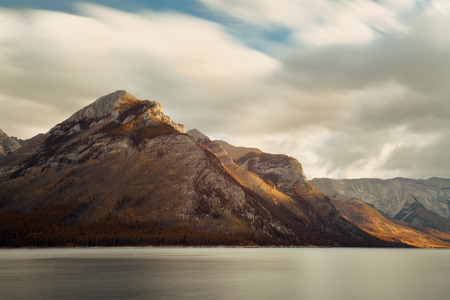 banff national park: Lake Minnewanka in Banff national park with mountains and forest in Canada at sunrise. Stock Photo
