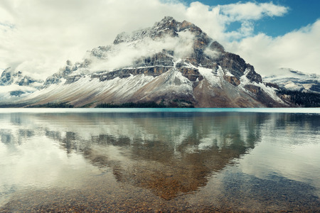 banff national park: Mountains and forest reflection at Bow Lake with fog in Banff National Park, Canada. Stock Photo
