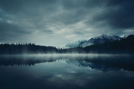 snow capped mountain: Lake Herbert in a foggy morning with glaciers mountain and reflection in Banff National Park, Canada