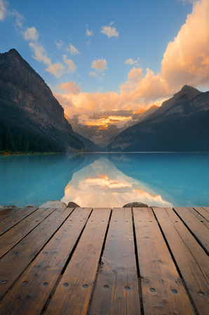 banff national park: Lake Louise with pier at sunrise in Banff national park with mountains and forest in Canada. Stock Photo