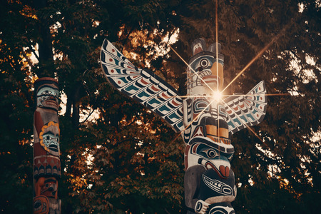 urban culture: Indian totem poles with sun ray in Stanley park in Vancouver, Canada. Stock Photo
