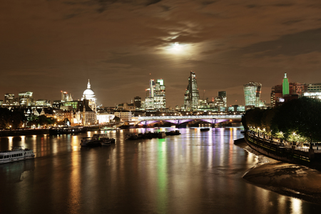 historical reflections: London cityscape with urban buildings and moon over Thames River at night Stock Photo