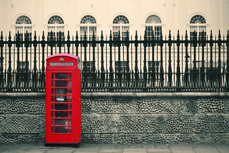 british english: Red telephone box in street with historical architecture in London. Stock Photo