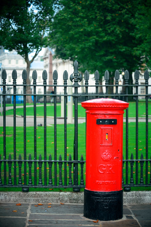 historical architecture: Red post box in street with historical architecture in London.