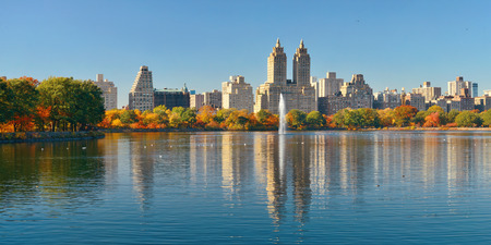 Skyline panorama with apartment skyscrapers over lake with fountain in Central Park in midtown Manhattan in New York City Stock Photo