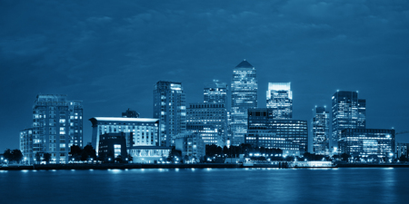 blackwhite: Canary Wharf business district in London at night over Thames River.