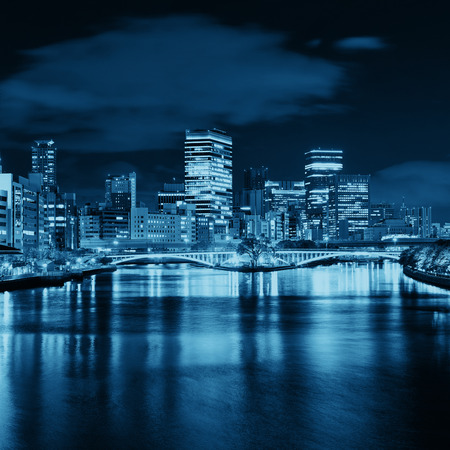 metropolis: Osaka skyline over river with skyscrapers and bridge. Japan.
