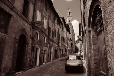 brick building: Street view with old buildings and bell tower in Siena, Italy. Stock Photo