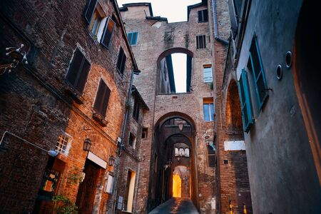 archways: Street view with old buildings and archway in Siena, Italy. Stock Photo