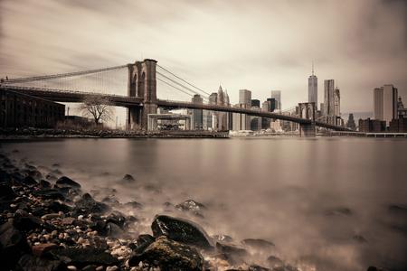 ブルックリン ブリッジとニューヨーク市のマンハッタンのダウンタウンのスカイラインの小石のビーチ