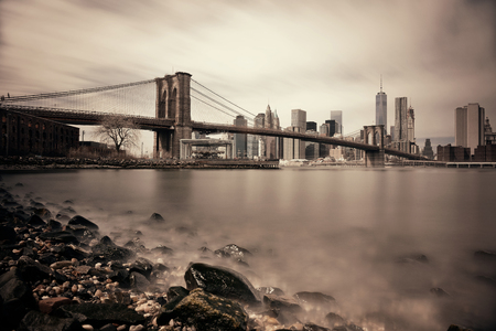 Kiezelstrand met Brooklyn Bridge en het centrum van de skyline van Manhattan in New York City