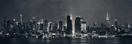 city night: Manhattan midtown skyscrapers and New York City skyline panorama at night with fog