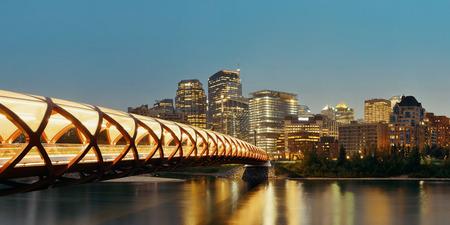 カルガリー平和橋と夜、カナダ アルバータ州のダウンタウンの高層ビルと街並み。