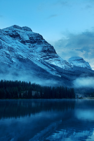 Snow capped mountain with lake reflection in a foggy dusk in Banff National Park, Canada.