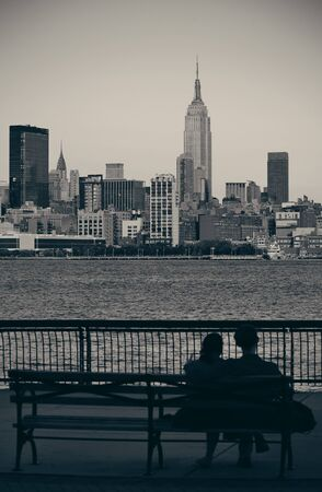 Couple rest on bench watching New York City skyscrapers Imagens - 71939042