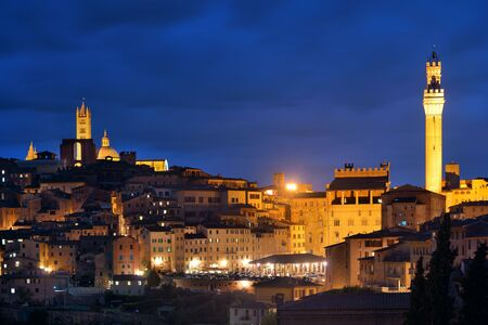 Medieval town Siena skyline view with Bell Tower and historic buildings in Italy at night Banco de Imagens
