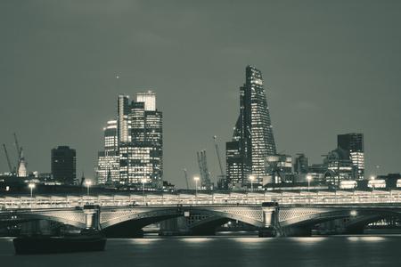 Blackfriars Bridge and London skyline at night.