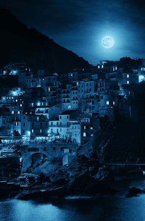 Manarola overlook Mediterranean Sea and moonrise with buildings over cliff in Cinque Terre at night, Italy. Stock Photo