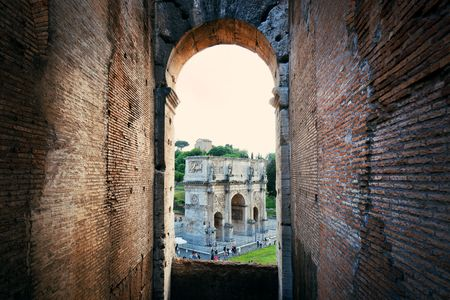 amphitheatre: Archway in Colosseum with Arch of Constantine, the world known landmark and the symbol of Rome, Italy.