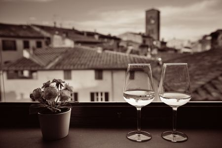 Window view with flower pot, glass of wine and historic buildings background in Lucca Italy