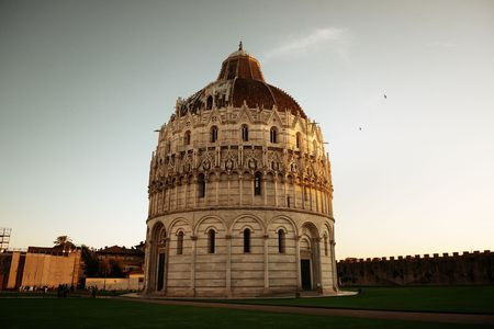 Pisa Piazza dei Miracoli with church dome in Italy at sunset