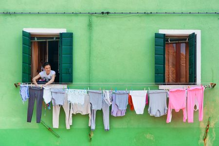 BURANO - MAY 27: Woman working on laundry on May 27, 2016 in Burano, Venice, Italy. Burano is a town featured with colorful houses northeast of Venice Island.