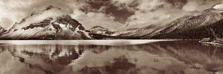 Bow Lake panorama reflection with snow capped mountain and forest in Banff National Park Stock Photo
