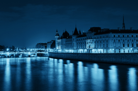 River Seine and bridge at night in Paris, France.