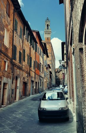Street view with old buildings and bell tower in Siena, Italy. Stock Photo