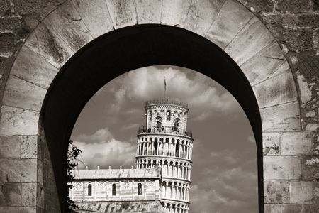 Leaning tower in Pisa through arch gate, Italy as the worldwide known landmark. Stock Photo