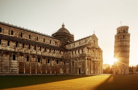 Leaning tower and cathedral at sunrise in Pisa, Italy as the worldwide known landmark. Stock fotó