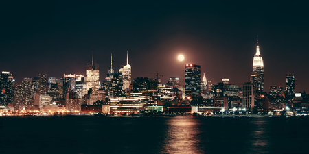 Moon rise over midtown Manhattan with city skyline at night 写真素材