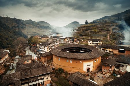 FUJIAN, CHINA – Aerial view of small rural village with Tulou. Tulou is the unique traditional rural dwelling of Hakka.