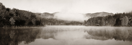 Lake fog panorama with Autumn foliage and mountains with reflection in New England Stowe Standard-Bild