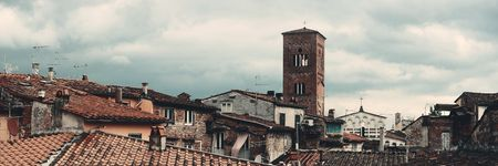 Tower of Chiesa San Pietro with roofs of historic buildings panorama view in Lucca, Italy.
