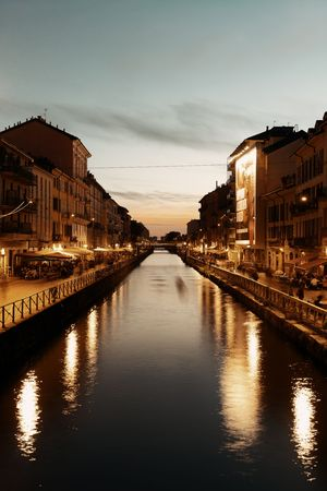 Naviglio Grande canal night life after sunset with restaurant and bars in Milan, Italy.