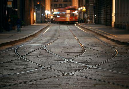 Tram track in street in Milan, Italy at night.